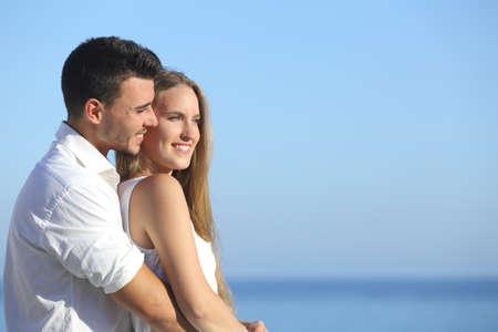 mujer mirando el horizonte: Atractiva pareja flirteo y abrazos mirando al futuro con el mar de fondo
