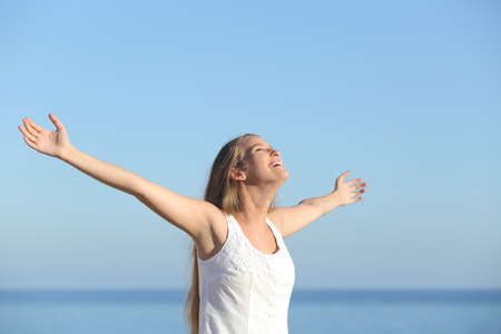 arms raised: Beautiful blonde woman breathing happy with raised arms with the sky in the background