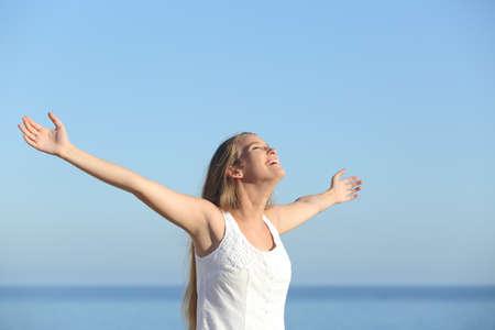 Mooie blonde vrouw ademt blij met opgeheven armen met de hemel op de achtergrond