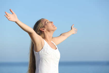 Attractive blonde woman breathing happy with raised arms with the sea in the background              版權商用圖片