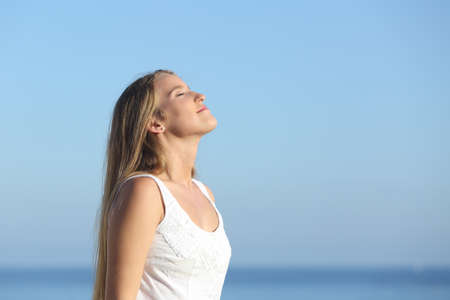Beautiful blonde woman breathing happy with the blue sky in the background Stok Fotoğraf