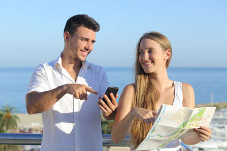 woman searching: Couple discussing map or smartphone gps on vacations with the sea in the background