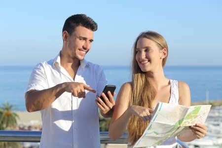 finding: Pareja discutiendo mapa o smartphone gps en las vacaciones con el mar de fondo
