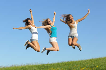 euphoria: Group of three teenager girls jumping on the grass with the blue sky in the background                 Stock Photo
