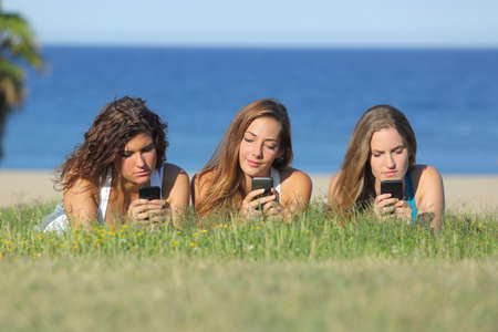 mobile telephones: Group of three teenager girls typing on the mobile phone lying on the grass with the sea in the background Stock Photo