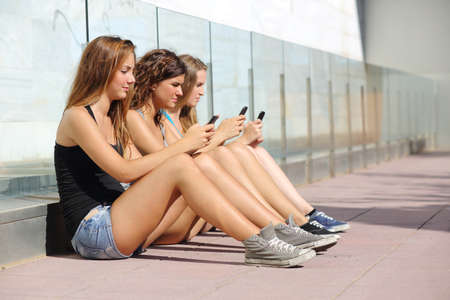Group of three teenager girls sitting on the floor typing on the mobile phone photo