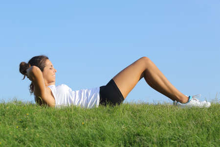 Side view of a beautiful woman doing crunches on the grass with the sky in the background