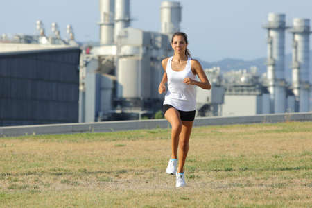 Front view of a beautiful woman running on the grass with a factory in the background photo
