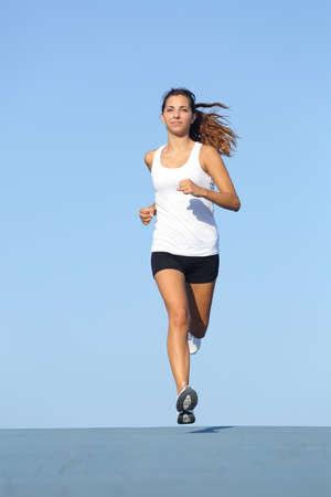 Vooraanzicht van een prachtige sportvrouw loopt naar de camera met de blauwe lucht op de achtergrond