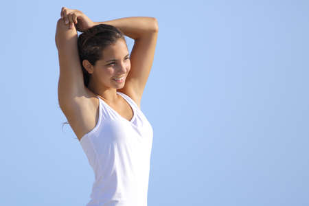 Attractive woman stretching arms outdoor with the blue sky in the background                photo