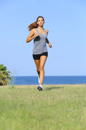 woman working out: Front view of a beautiful woman running on the grass with the sky and the sea in the background Stock Photo