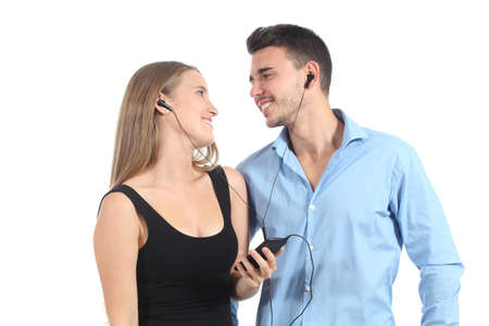 Attractive couple sharing music with a headphones isolated on a white background photo