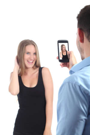 Man taking photograph of a girl with a mobile phone isolated on a white background              photo