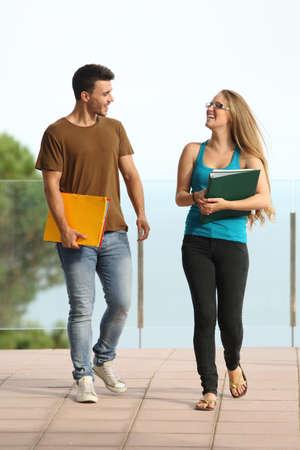 Adolescente estudiantes niño y niña caminando hacia la cámara y sonriendo Foto de archivo - 22038083