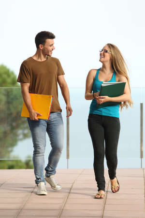 couple talking: Teenager students boy and girl walking towards camera and smiling Stock Photo