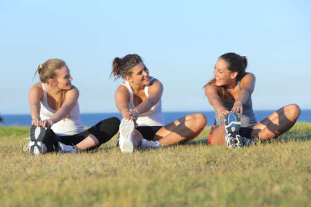 Group of three women stretching after sport on the grass with the sea in the background             photo