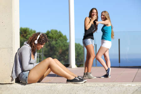 Two teen girls bullying and making fun and pointing another one  photo