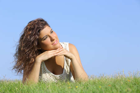 blue sky thinking: Portrait of a beautiful woman lying on the grass with a blue sky in the background