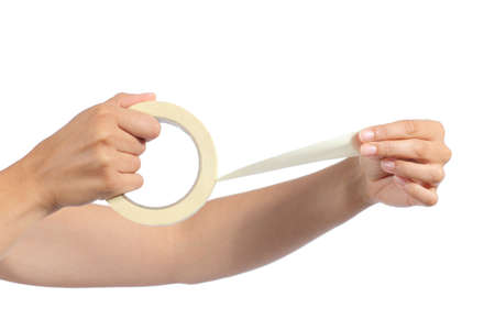 Woman hands holding and using a masking tape isolated on a white background               photo
