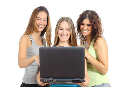 Group of teenager girls browsing internet in a laptop and smiling  isolated on a white background               photo