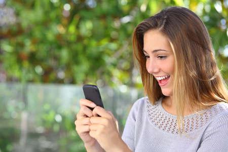 Mooie vrouw surfen op internet gelukkig in haar slimme telefoon met een groene achtergrond
