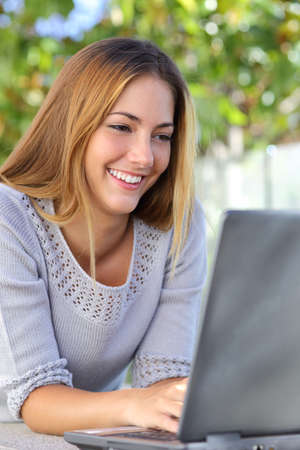Beautiful woman happy browsing internet in her laptop outdoor           photo