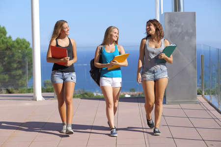 Group of three student teenagers walking towards camera with the sky in the background photo