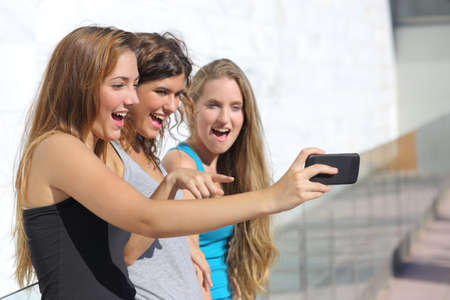 Group of three teenager girls amazed watching the smart phone outdoor photo