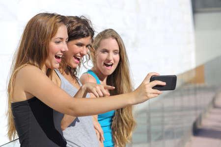 sch�ne frauen: Gruppe von drei Teenager M�dchen erstaunt beobachtete das Smartphone im Freien