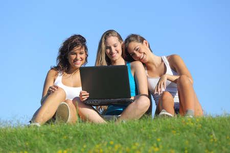 mujer mirando el horizonte: Grupo de tres chicas adolescentes riendo mientras mira la computadora port�til sentados en el c�sped con el cielo en el fondo Foto de archivo