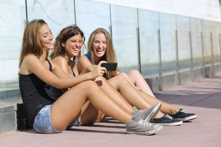 Group of three teenager girls sitting on the floor laughing while watching the smart phone photo