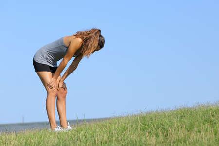 Fitness vrouw moe rusten op het gras met de hemel op de achtergrond