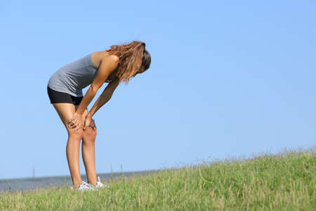 Fitness woman tired resting on the grass with the sky in the background photo