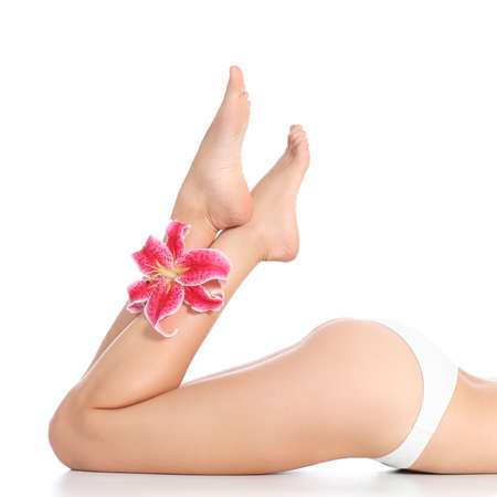 Beautiful smooth and waxed woman legs and feet with a flower isolated on a white background