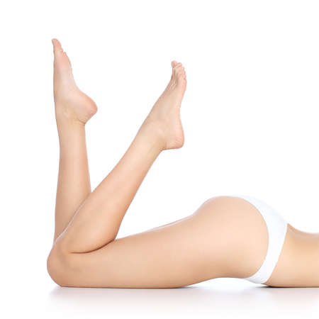 Perfect smooth and waxed woman legs with feet pointing up isolated on a white background           photo