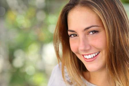 s úsměvem: Krásná žena s vybělit perfektní úsměv venkovní se zeleným pozadím