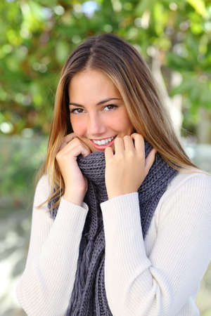 Happy beautiful woman keeping warm with a sweater and a scarf outdoor in a cold winter            photo