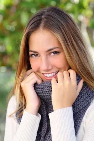 grabbing hand: Close up of a beautiful woman smiling outdoor in winter with a green background