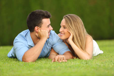first sight: Couple in love dating and looking each other lying on the grass with a green background