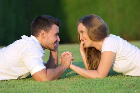 Profil d'un couple amoureux flirtant et en regardant les uns les autres couchés sur l'herbe avec un fond vert Banque d'images - 22400167