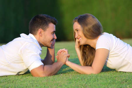 love at first sight: Profile of a couple in love flirting and looking each other lying on the grass with a green background
