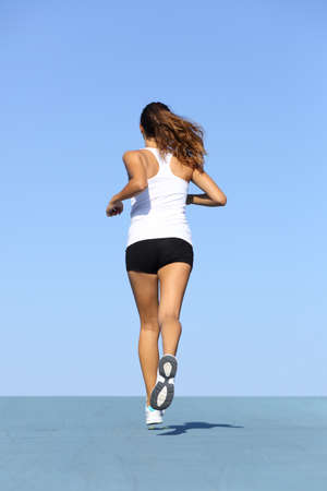 woman running: Back view of a fitness woman running on blue with the horizon in the background Stock Photo