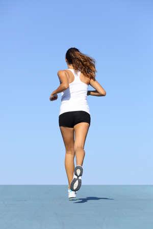 mujeres corriendo: Vista posterior de una mujer de la aptitud que se ejecutan en azul con el horizonte en el fondo Foto de archivo
