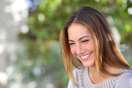 friendly people: Beautiful woman laughing happy outdoor with a green unfocused background               Stock Photo