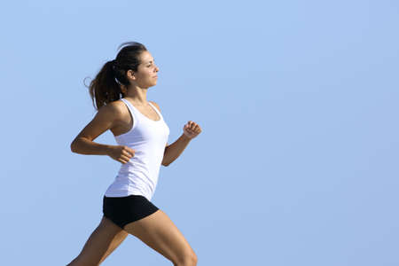 Side view of a fitness woman running fast with the sky in the background photo