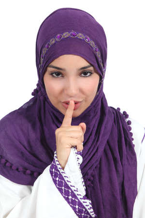 Beautiful arab woman asking for silence with the finger on lips isolated on a white background            photo