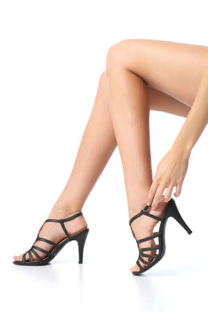 Woman with beautiful legs touching the heel of the foot isolated on a white background