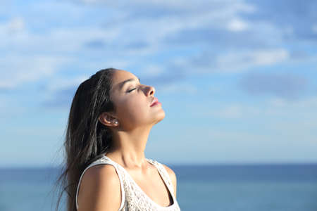 Beautiful arab woman breathing fresh air in the beach with a cloudy blue sky  Stock Photo