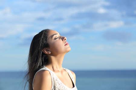 Mooie Arabische vrouw inademen van frisse lucht in het strand met een bewolkte blauwe hemel