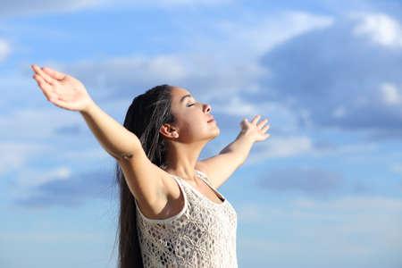 Mooie Arabische vrouw inademen van frisse lucht met opgeheven armen met een bewolkte blauwe hemel Stockfoto